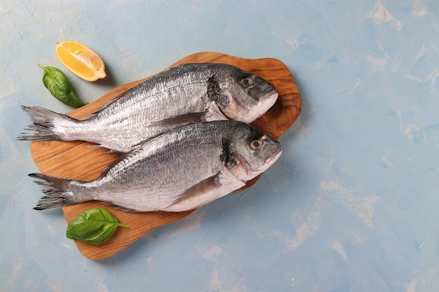 Dois peixes dourados crus com manjericão e limão na tábua de madeira