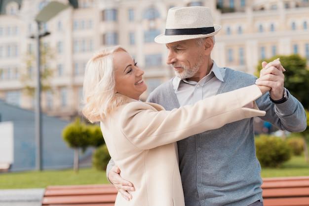 Dois pensionistas dançam na praça perto do banco