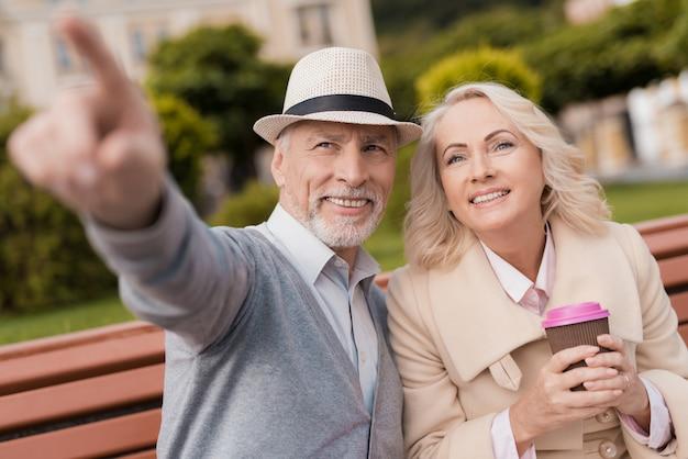 Dois pensionistas estão sentados em um banco com um copo de café
