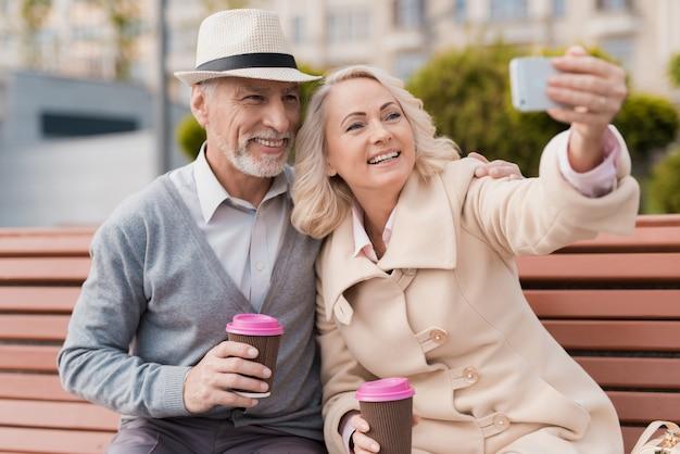 Dois pensionistas estão sentados no banco com um copo de café.
