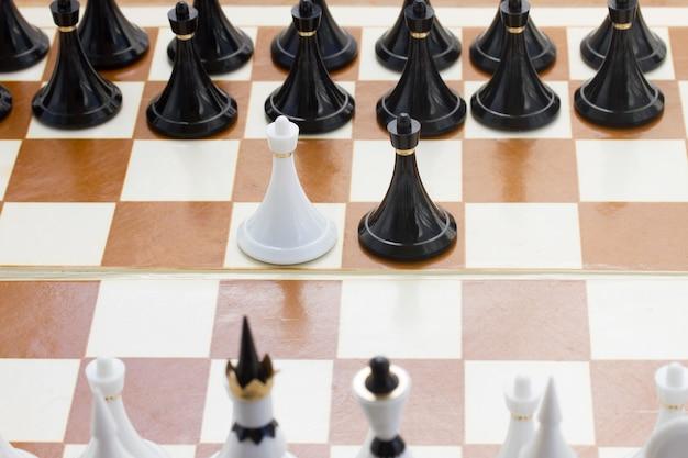 Dois peões brancos e pretos na frente do xadrez preto