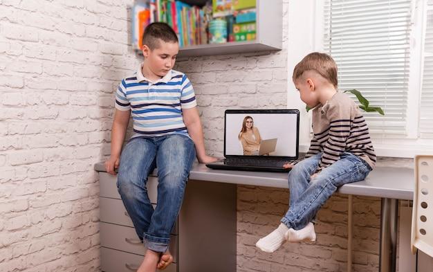 Dois pequenos amigos felizes. meninos usando tablet digital inteligente em casa.
