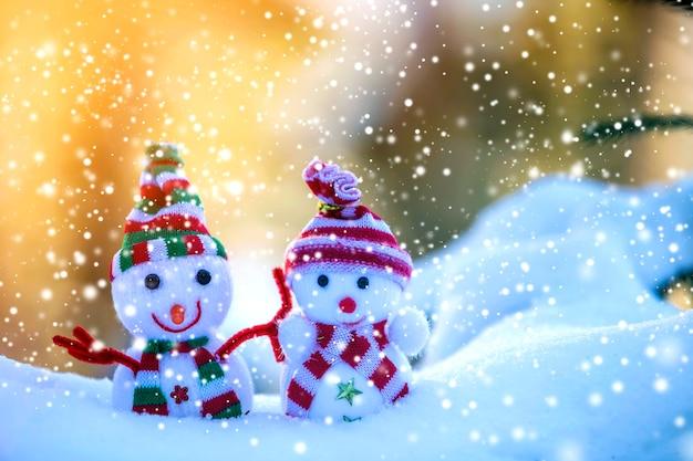 Dois pequenos brinquedos engraçados bebê boneco de neve em chapéus de malha e cachecóis na neve profunda ao ar livre em azul e branco brilhante cópia espaço de fundo. cartão de feliz ano novo e feliz natal.