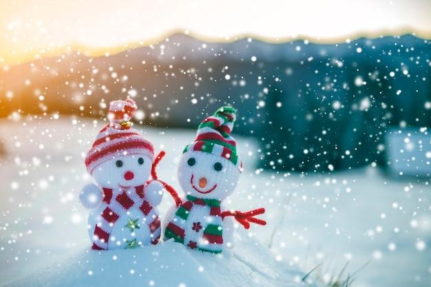 Dois pequenos brinquedos engraçados bebê boneco de neve em chapéus de malha e cachecóis na neve profunda ao ar livre em montanhas borradas paisagem fundo. tema de cartão de feliz ano novo e feliz natal.