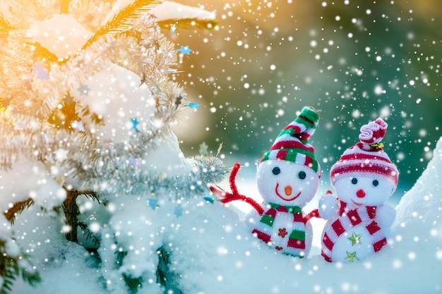 Dois pequenos brinquedos engraçados bebê boneco de neve em chapéus de malha e cachecóis na neve profunda ao ar livre perto de galho de pinheiro. cartão de feliz ano novo e feliz natal.