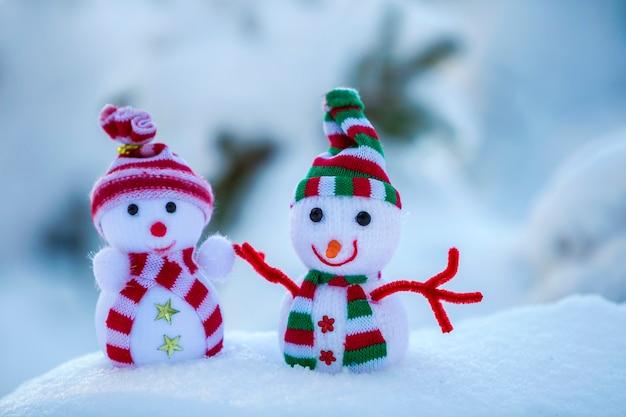 Dois pequenos brinquedos engraçados bebê boneco de neve em chapéus de malha e lenços na neve profunda ao ar livre em azul e branco brilhante cópia espaço fundo. cartão de feliz ano novo e feliz natal.