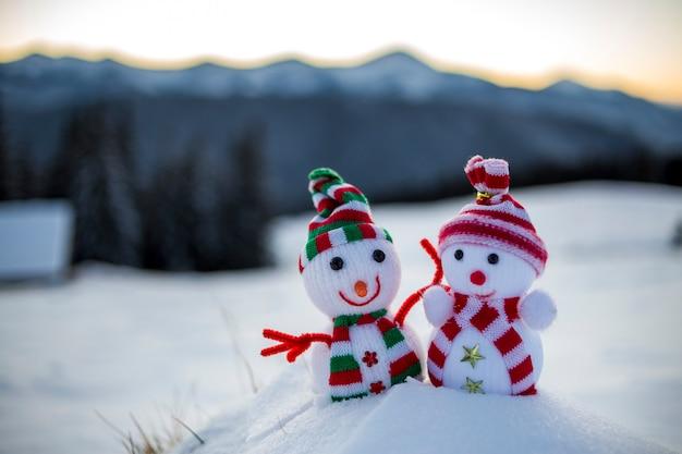 Dois pequenos brinquedos engraçados bebê boneco de neve em chapéus de malha e lenços na neve profunda ao ar livre