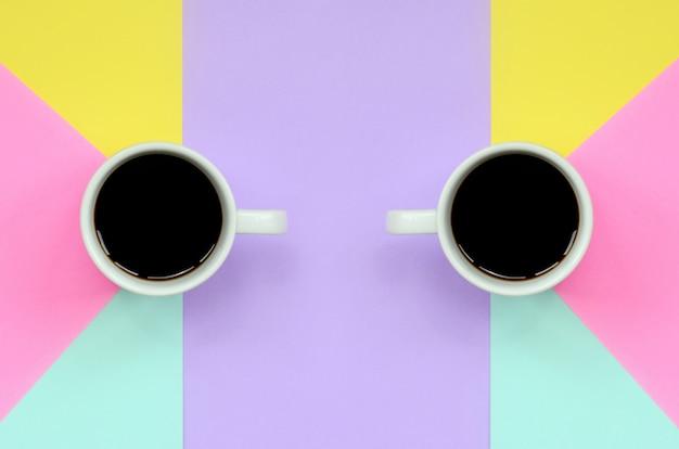 Dois pequenos copos de café branco sobre fundo de textura