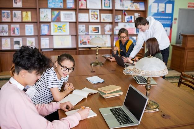 Dois pequenos grupos de estudantes universitários contemporâneos sentados em mesas e discutindo seus planos ou pontos de projetos na biblioteca