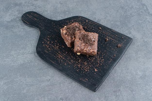 Dois pequenos pedaços de brownie em um prato escuro