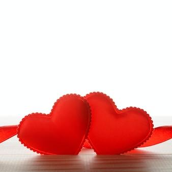 Dois pequenos tecido de coração e fita na mesa