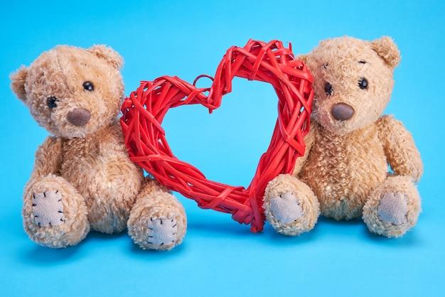 Dois pequenos ursos de pelúcia e um coração de vime decorativo vermelho