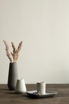 Dois pequenos vasos de cerâmica branca sobre uma mesa de madeira, um maior preto com grama seca na parede do quarto doméstico