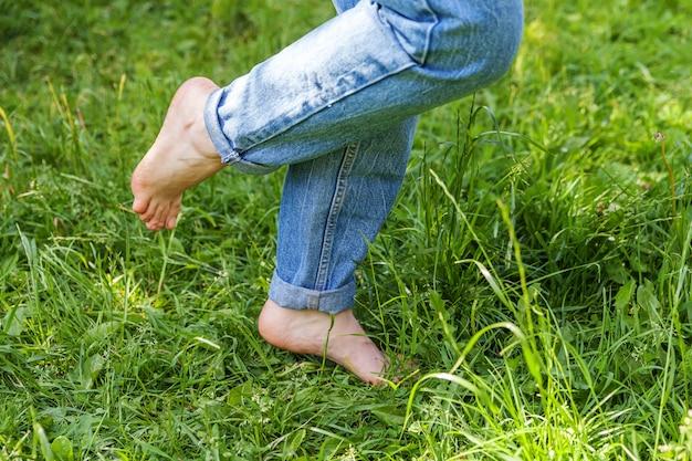 Dois pés femininos bonitos andando na grama na manhã ensolarada de verão. pernas de menina descalça passo leve no gramado macio da primavera no jardim ou parque. liberdade saudável relaxar conceito.