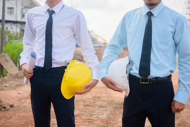 Dois, pessoas negócio, segurando, capacete segurança, ficar, ao ar livre, projeto equipe gerenciamento