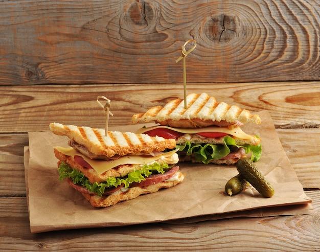 Dois picles de sanduíche em papel kraft na superfície de madeira