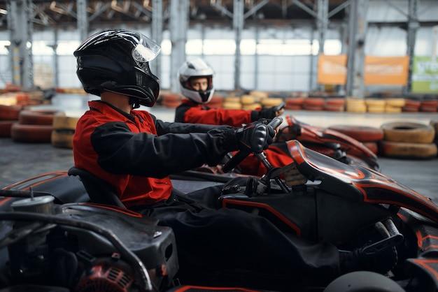 Dois pilotos de kart lutam pela vitória na volta, vista lateral, karting automobilístico interno. corrida de velocidade em pista fechada de kart com barreira de pneus. competição de veículos velozes, lazer com alta adrenalina