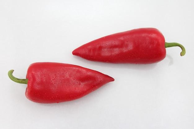 Dois pimentões vermelhos brilhantes em um branco