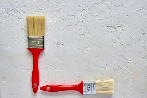 Dois pincéis com alças vermelhas em concreto fresco. conceito de reparação. vista superior com espaço de cópia