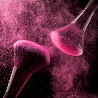 Dois pincéis cosméticos e pó-de-rosa sobre fundo escuro