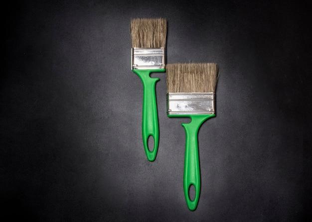 Dois pincéis verdes sobre um plano de fundo texturizado preto com uma vinheta.