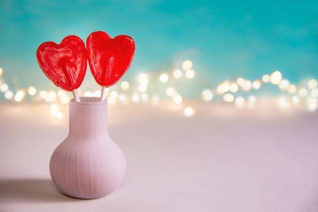 Dois pirulitos de doces de forma de coração vermelho em varas no vaso fundo turquesa com espumante luzes de bokeh dos namorados