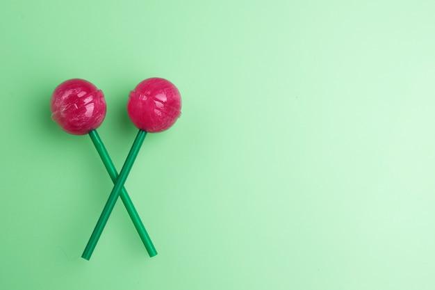 Dois pirulitos no fundo da cor pastel da hortelã. conceito de pirulito.