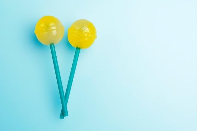 Dois pirulitos saborosos amarelos brilhantes grandes em varas verdes no fundo pastel azul.