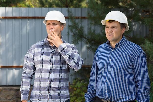 Dois planejadores de edifício masculino de meia-idade visitando o local do projeto enquanto observam o andamento da construção.