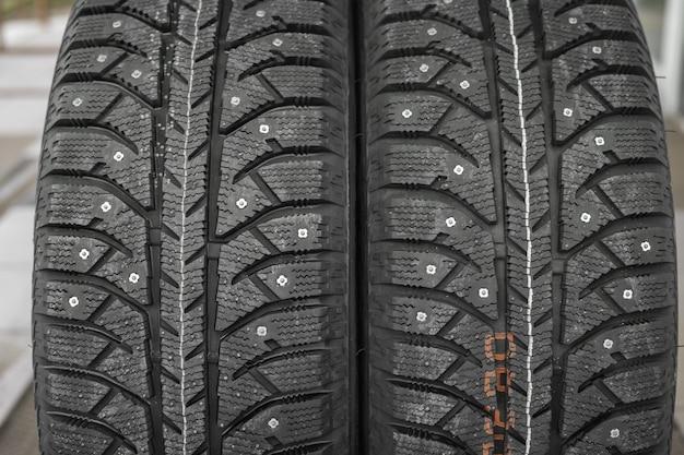 Dois pneus com pregos de inverno, close-up