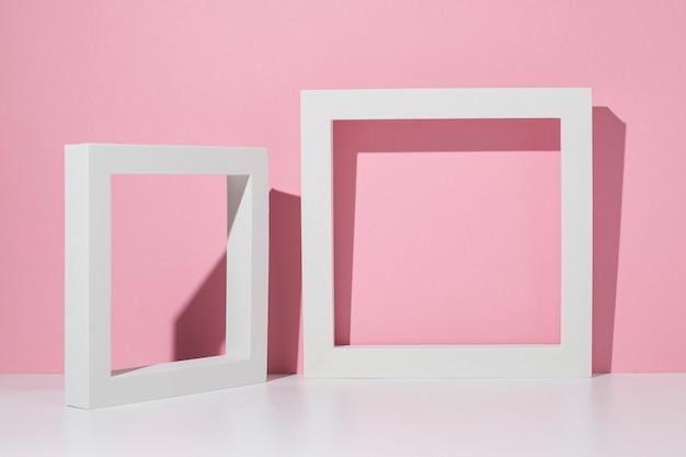 Dois pódios quadrados brancos para apresentação em um fundo branco e rosa.