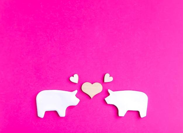 Dois porcos de barro feitos à mão com pequenos corações de madeira em fundo rosa brilhante, cartão de dia dos namorados ou elementos de design de cartaz.