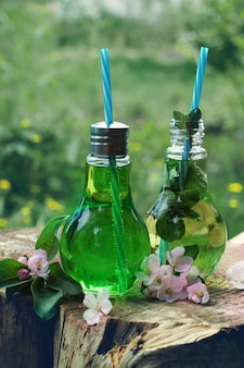 Dois potes com tubos em forma de lâmpadas cheios de limonada ficam em um toco ao ar livre.