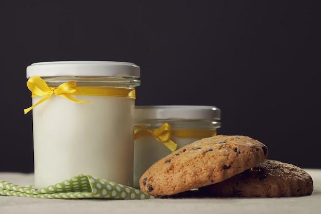 Dois potes de leite e biscoitos com fita amarela em um escuro