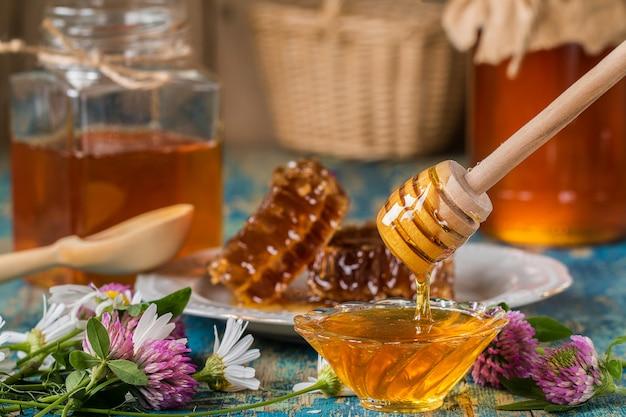 Dois potes de mel com favo de mel em uma mesa de madeira com flores