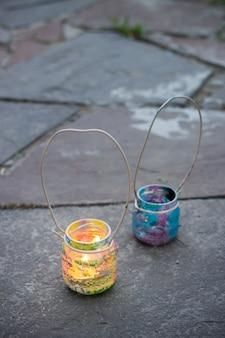 Dois potes de vidro coloridos com lâmpadas de vela com alça de arame em azulejos externos de pedra, atividades infantis e conceito de ideia artesanal vertical