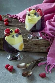Dois potes de vidro com sobremesa fria (panna cotta, geléia, musse, pudim) com camadas de mirtilo roxo e banana branca em mesa rústica de madeira