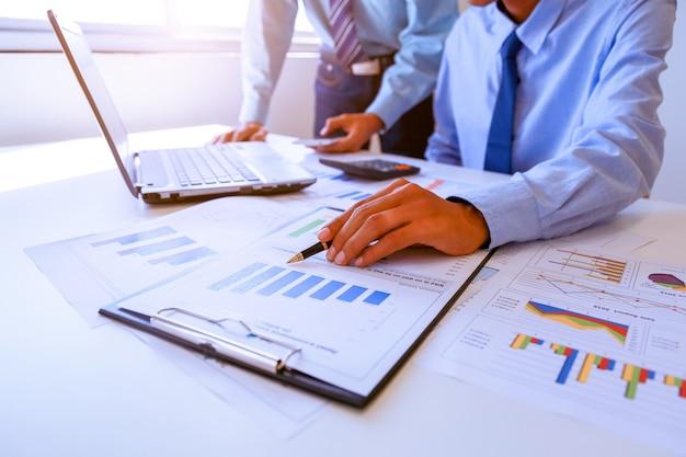 Dois povos do homem de negócio que trabalham analisando e calculam o sumário.