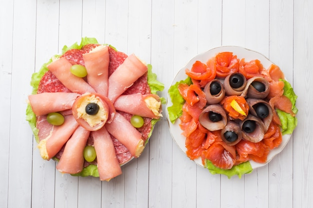 Dois pratos de aperitivos. rolinho de presunto com queijo e peixe vermelho