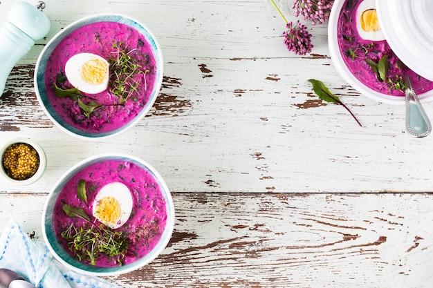 Dois pratos de beterraba fria de verão, pepino e sopa de ovo em uma mesa de madeira. vista do topo. copie o espaço.
