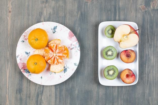 Dois pratos de frutas diversas na superfície de madeira