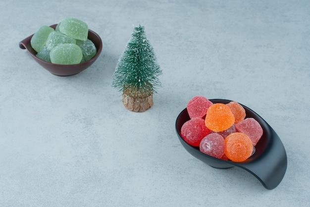 Dois pratos escuros de geleia de açúcar com pequena árvore de natal. foto de alta qualidade