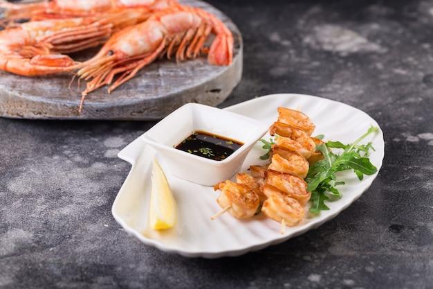 Dois pratos espetada de salmão grelhado com limão e molho em um prato branco e camarões grandes em uma placa de madeira.