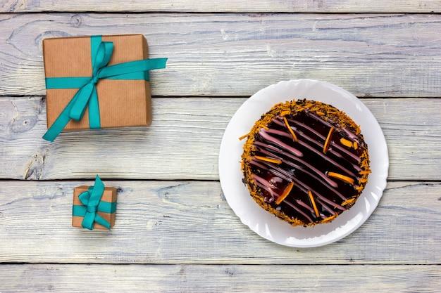 Dois presentes embrulhados em papel artesanal e um bolo de chocolate sobre uma mesa de luz.
