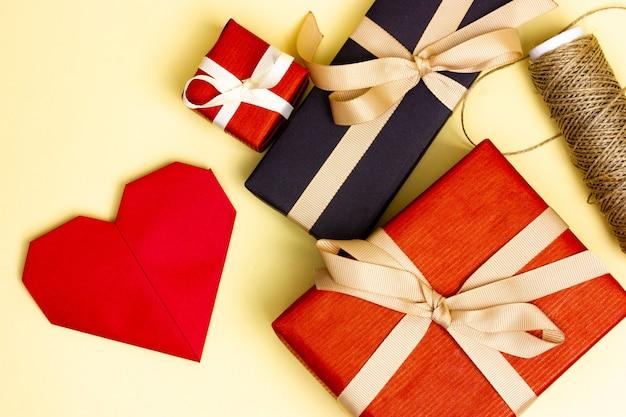 Dois presentes vermelhos e um preto sobre um fundo amarelo. cartão postal em forma de um coração vermelho. vista de cima.
