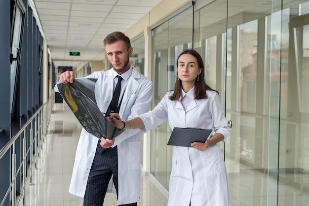 Dois profissionais de saúde observando a imagem de raio-x, ressonância magnética do paciente para diagnóstico e tratamento no hospital