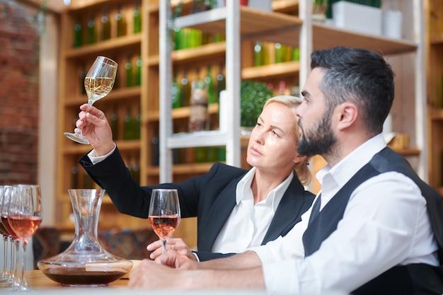 Dois profissionais sentados no local de trabalho enquanto observam uma amostra de vinho branco em um copo de vinho e avaliam sua cor