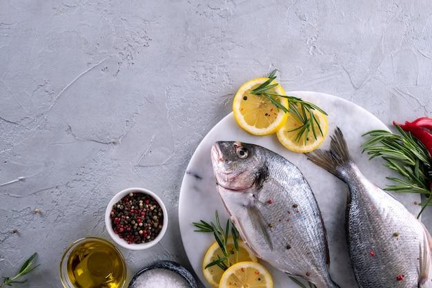 Dois prontos para cozinhar o peixe cru com ervas, limão e azeite na placa de mármore em fundo cinza. com espaço de cópia. vista do topo