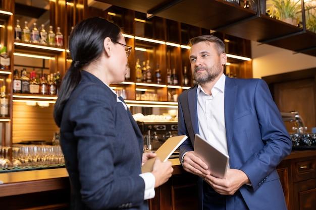 Dois proprietários de restaurante luxuoso em pé junto ao balcão do bar, consultando sobre alguns momentos de trabalho