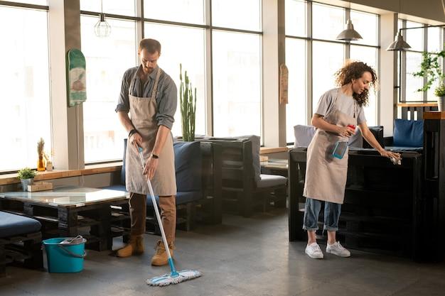 Dois proprietários de restaurante ou café contemporâneo lavando o chão e desinfetando móveis com desinfetante após o dia de trabalho